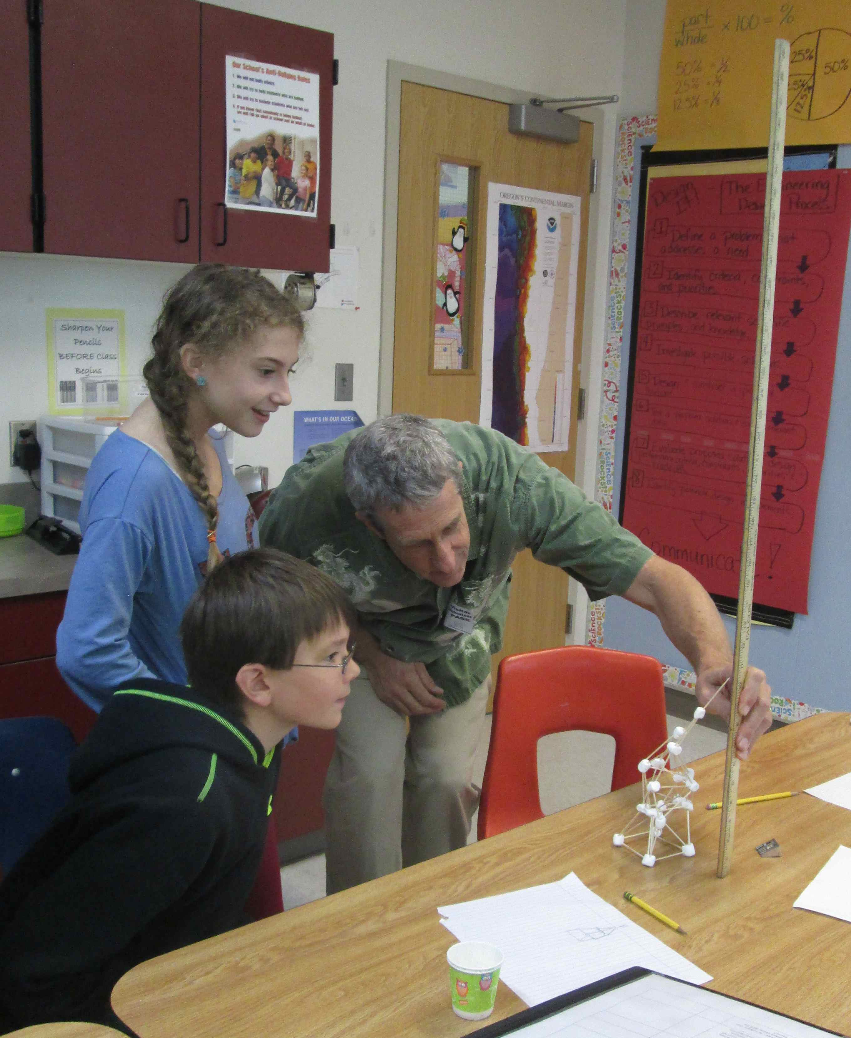 A science fair mentor helps 6th graders evaluate their engineering design
