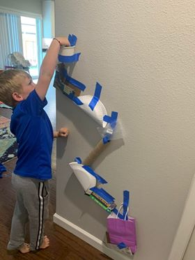 Child tests a paper tube raceway