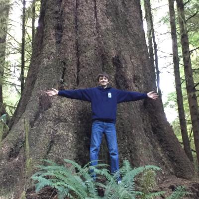 Boy stands in front of big tree