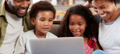 family sits on couch together and looks at laptop computer