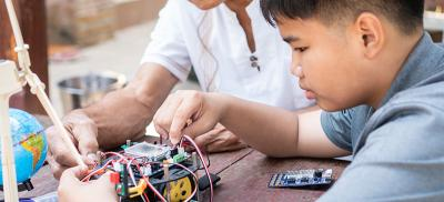 Grandfather and grandson work together on an electronics project