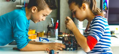 male and female middle schoolers engaged in STEM at home