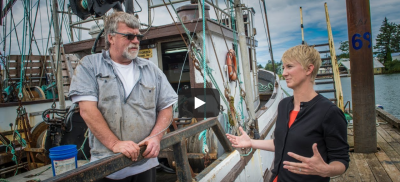Fisherman and Sea Grant Fisheries Extension agent talk on a dock